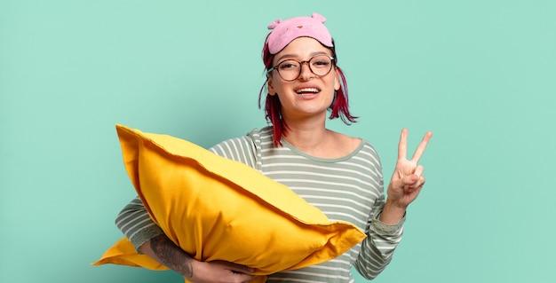 Mulher jovem e atraente de cabelo ruivo sorrindo e parecendo amigável, mostrando o número dois ou o segundo com a mão para a frente, em contagem regressiva e de pijama.