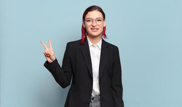 Mulher jovem e atraente de cabelo ruivo sorrindo e parecendo amigável, mostrando o número dois ou o segundo com a mão para a frente, em contagem regressiva