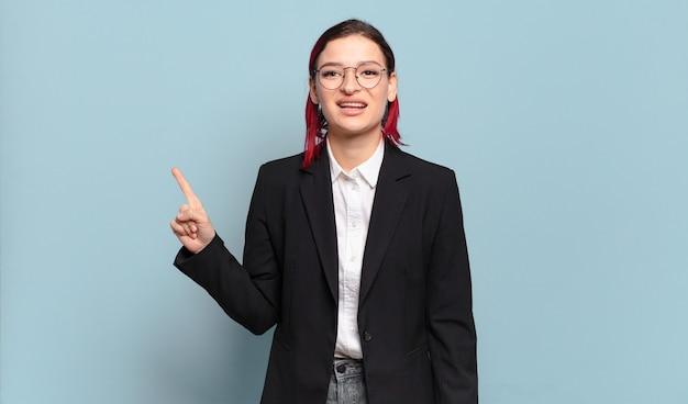 Mulher jovem e atraente de cabelo ruivo sorrindo e parecendo amigável, mostrando o número um ou primeiro com a mão para a frente