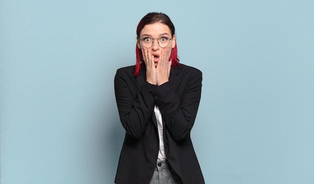 Mulher jovem e atraente de cabelo vermelho chocada e assustada, parecendo apavorada com a boca aberta e as mãos nas bochechas