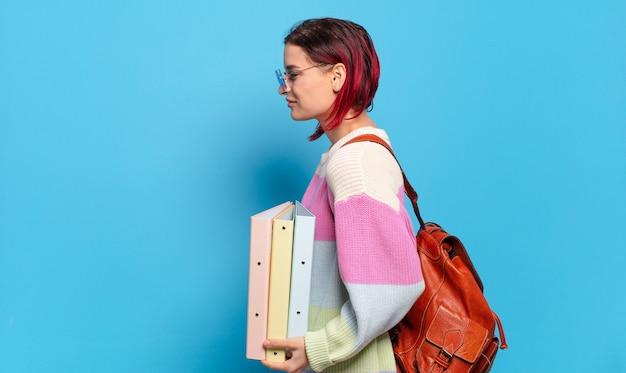 Mulher jovem e atraente de cabelo vermelho em vista de perfil, olhando para copiar o espaço à frente, pensando, imaginando ou sonhando acordado. conceito de estudante universitário