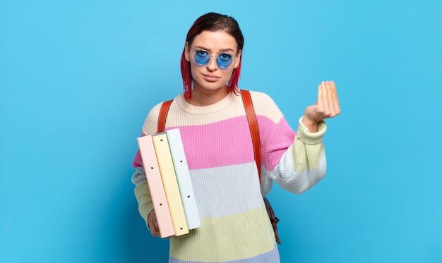 Mulher jovem e atraente de cabelo vermelho fazendo capice ou gesto de dinheiro, dizendo para você pagar suas dívidas !. conceito de estudante universitário