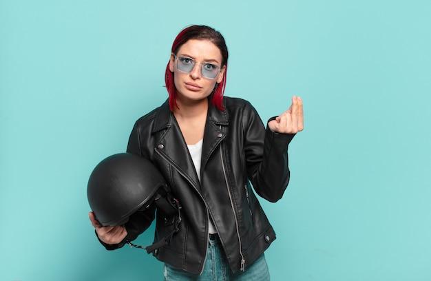 Mulher jovem e atraente de cabelo vermelho fazendo capice ou gesto de dinheiro, dizendo para você pagar suas dívidas !. conceito de motociclista