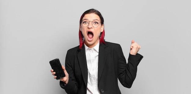 Mulher jovem e atraente de cabelo vermelho gritando agressivamente com uma expressão de raiva ou com os punhos cerrados, celebrando o sucesso. conceito de negócios