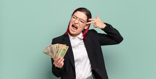 Mulher jovem e atraente de cabelo vermelho olhando infeliz e estressada, gesto de suicídio fazendo sinal de arma com a mão, apontando para a cabeça. conceito de dinheiro