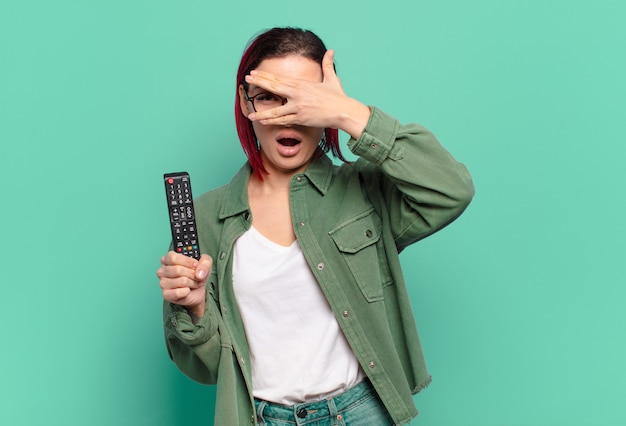Mulher jovem e atraente de cabelo vermelho parecendo chocada, assustada ou apavorada, segurando um controle remoto de tv