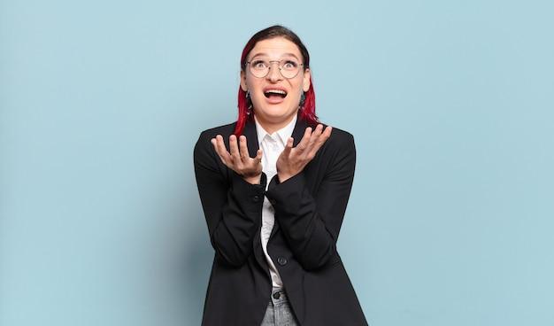 Mulher jovem e atraente de cabelo vermelho parecendo desesperada e frustrada, estressada, infeliz e irritada, gritando e gritando