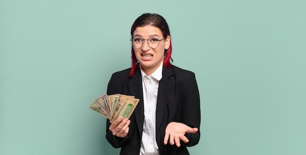 Mulher jovem e atraente de cabelo vermelho parecendo zangada, irritada e frustrada gritando wtf ou o que há de errado com você. conceito de dinheiro