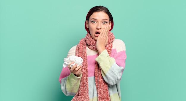 Mulher jovem e atraente de cabelo vermelho se sentindo chocada e assustada, parecendo apavorada com a boca aberta e as mãos nas bochechas conceito de gripe