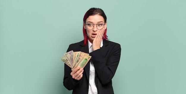 Mulher jovem e atraente de cabelo vermelho se sentindo chocada e com medo, parecendo apavorada com a boca aberta e as mãos nas bochechas. conceito de dinheiro