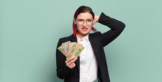 Mulher jovem e atraente de cabelo vermelho se sentindo estressada, preocupada, ansiosa ou com medo, com as mãos na cabeça, entrando em pânico por engano. conceito de dinheiro