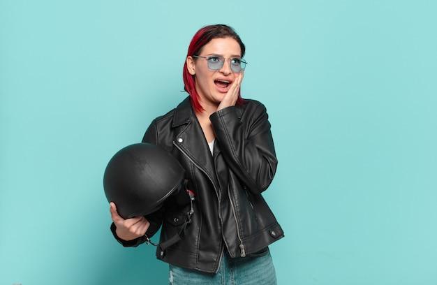 Mulher jovem e atraente de cabelo vermelho se sentindo feliz, animada e surpresa, olhando para o lado com as duas mãos no rosto. conceito de motociclista