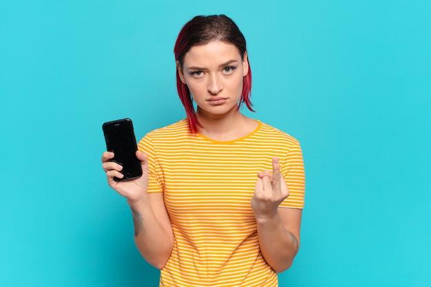 Mulher jovem e atraente de cabelo vermelho se sentindo irritada, irritada, rebelde e agressiva, sacudindo o dedo do meio, lutando para trás e mostrando seu celular