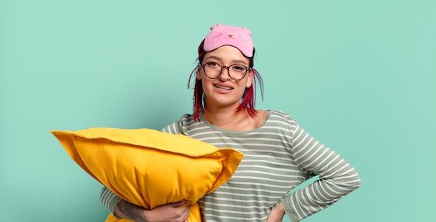 Mulher jovem e atraente de cabelo vermelho sorrindo alegremente com uma mão no quadril e uma atitude confiante, positiva, orgulhosa e amigável e de pijama.