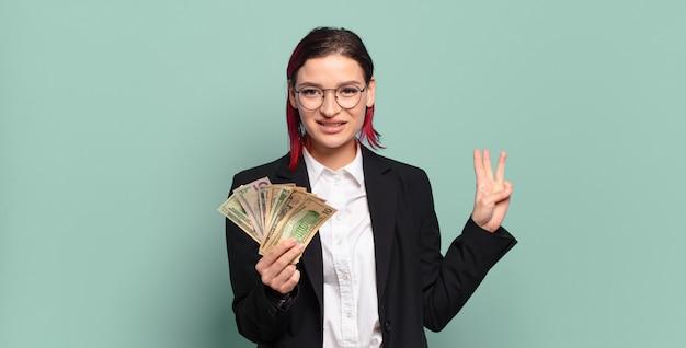 Mulher jovem e atraente de cabelo vermelho sorrindo e parecendo amigável, mostrando o número três ou terceiro com a mão para a frente, em contagem regressiva. conceito de dinheiro