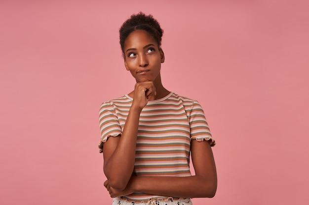 Mulher jovem e atraente de cabelos castanhos perplexa com penteado coque, apoiando o queixo na mão levantada enquanto olha pensativamente para cima, isolada sobre a parede rosa