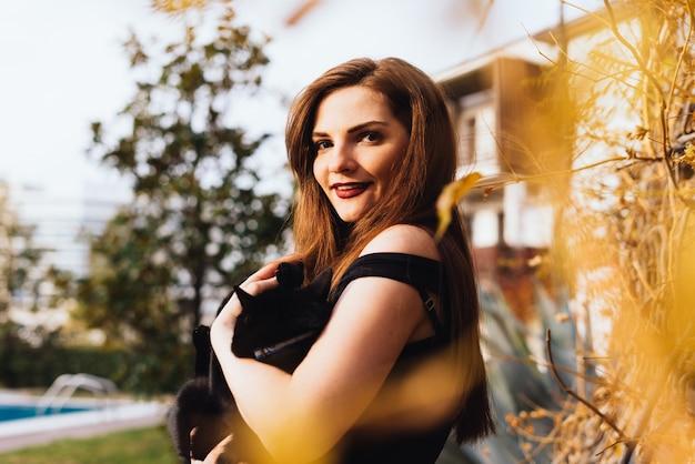Mulher jovem e atraente de cabelos compridos caminhando no parque, segurando um gato preto e sorrindo
