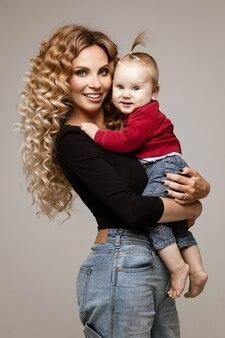 Mulher jovem e atraente de cabelos compridos vestindo roupas casuais em pé na parede cinza com uma criança nas mãos
