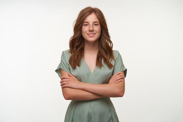 Mulher jovem e atraente de cabelos ruivos com penteado romântico usando um vestido vintage, com as mãos cruzadas no peito e com uma aparência positiva, isolada