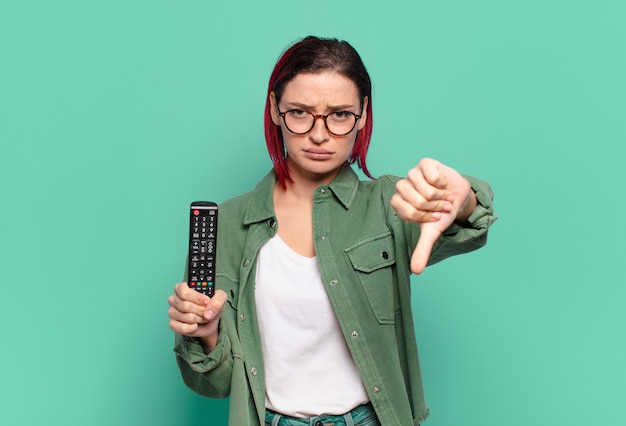 Mulher jovem e atraente de cabelos vermelhos se sentindo zangada, irritada, decepcionada ou descontente, mostrando os polegares para baixo com um olhar sério e segurando um controle remoto de tv