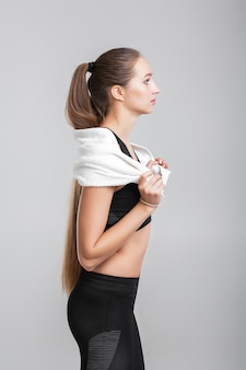 Mulher jovem e atraente de esportes com toalha após o treino