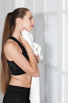 Mulher jovem e atraente de esportes com uma toalha após o treino perto da janela