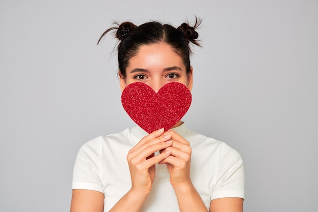 Mulher jovem e atraente de etnia alegre apaixonada segurando um grande dia dos namorados com um coração vermelho brilhante e cobrindo a boca e o nariz enquanto sorri com os olhos