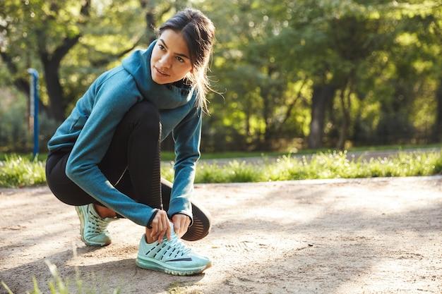 Mulher jovem e atraente de fitness amarrando o cadarço ao ar livre