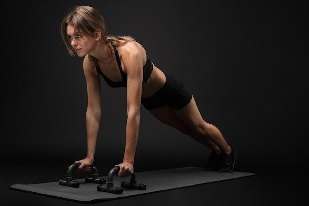 Mulher jovem e atraente de fitness saudável usando sutiã esportivo e shorts isolados sobre um fundo preto, se exercitando em uma esteira de fitness