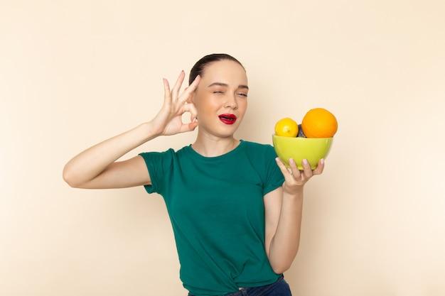 Mulher jovem e atraente de frente com camisa verde escura segurando um prato com frutas