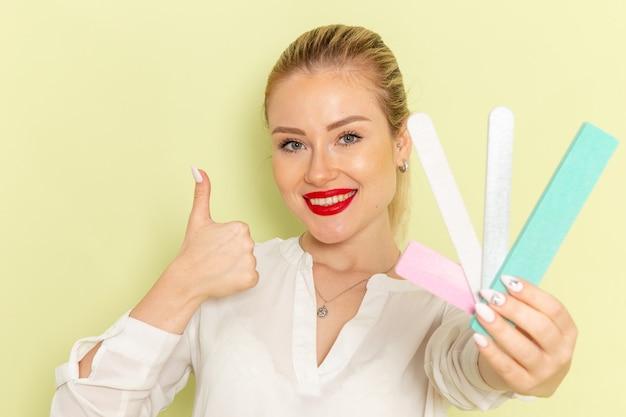 Mulher jovem e atraente de frente com uma camisa branca segurando diferentes acessórios de manicure e sorrindo na superfície verde