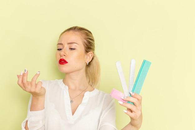 Mulher jovem e atraente de frente, de camisa branca, segurando acessórios de manicure na superfície verde