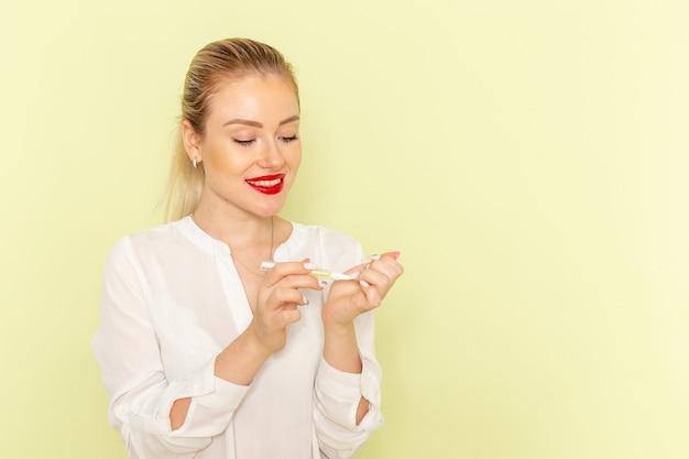 Mulher jovem e atraente de frente, de camisa branca, trabalhando com as unhas e sorrindo na superfície verde