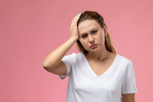 Mulher jovem e atraente de frente em camiseta branca com forte dor de cabeça no fundo rosa