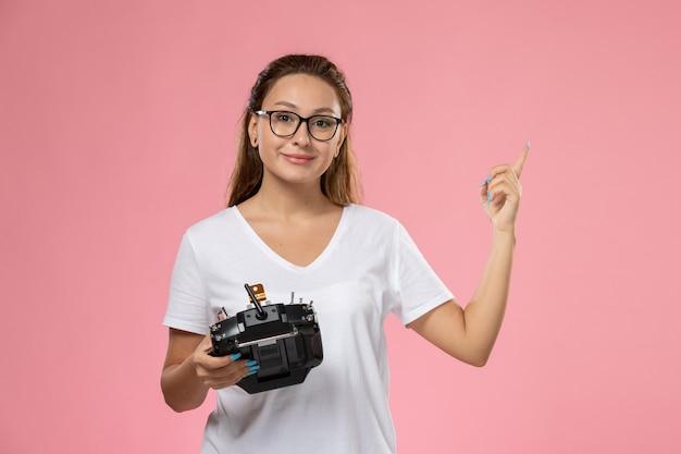 Mulher jovem e atraente de frente para a camiseta branca com expressão de descontentamento segurando o controle remoto na mesa rosa