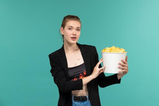 Mulher jovem e atraente de frente segurando cips e assistindo filme na superfície azul