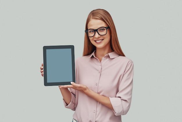 Mulher jovem e atraente de óculos apontando para o espaço da cópia no tablet digital e sorrindo em pé contra um fundo cinza