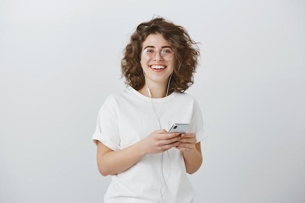 Mulher jovem e atraente de óculos sorrindo enquanto segura o smartphone e ouve música nos fones de ouvido