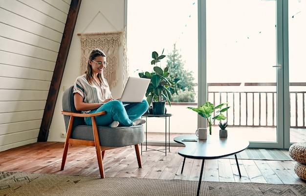 Mulher jovem e atraente de óculos trabalha em um laptop enquanto está sentado de pernas cruzadas em uma cadeira confortável em casa.