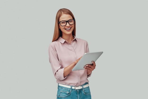 Mulher jovem e atraente de óculos usando tablet digital e sorrindo em pé contra um fundo cinza