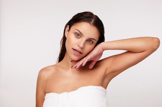 Mulher jovem e atraente de olhos verdes com cabelo molhado, tocando suavemente seu rosto com a mão levantada e olhando afetuosamente, posando com uma toalha de banho