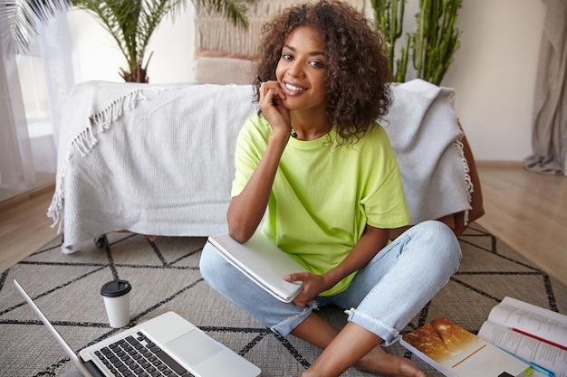 Mulher jovem e atraente de pele escura com cabelo castanho cacheado posando sobre o interior da casa, parecendo alegre e apoiada no queixo