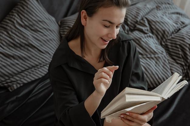 Mulher jovem e atraente de pijama é relaxante na cama enquanto lê um livro.