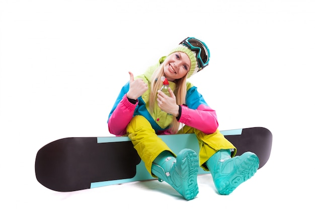Mulher jovem e atraente de terno de esqui e óculos de esqui, sentar no snowboard, segurar a água