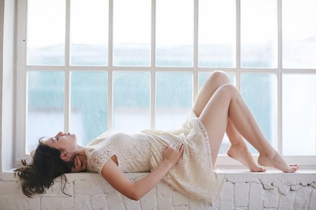 Mulher jovem e atraente deitada no parapeito de uma janela