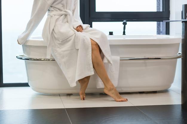 Mulher jovem e atraente descalça com roupão de banho branco sentada na banheira do banheiro