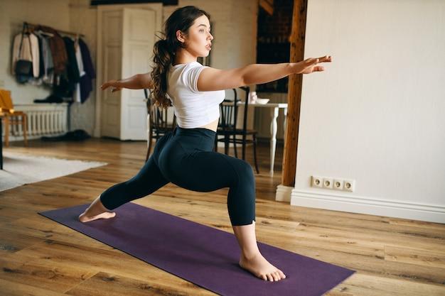 Mulher jovem e atraente descalça praticando ioga em casa, em pé no tapete, fazendo pose de guerreiro ii ou virabhadrasana, fortalecendo pernas, abrindo quadris e desenvolvendo concentração e equilíbrio