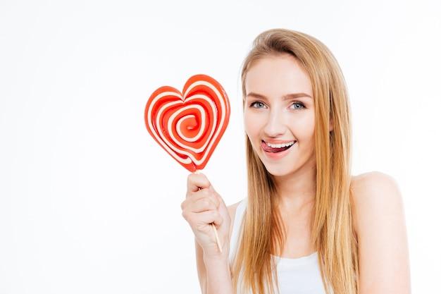 Mulher jovem e atraente divertida mostrando a língua e segurando um pirulito formador de coração sobre fundo branco