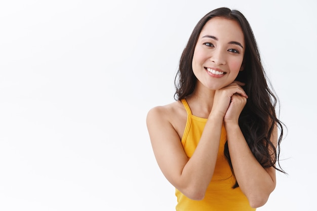 Mulher jovem e atraente do leste asiático suspirando de afeto e felicidade, mãos juntas perto do queixo, sorrindo alegre, olhar com amor e carinho