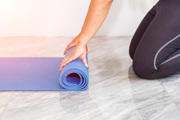 Mulher jovem e atraente dobrar ioga azul ou tapete de fitness depois de trabalhar em casa na sala de estar